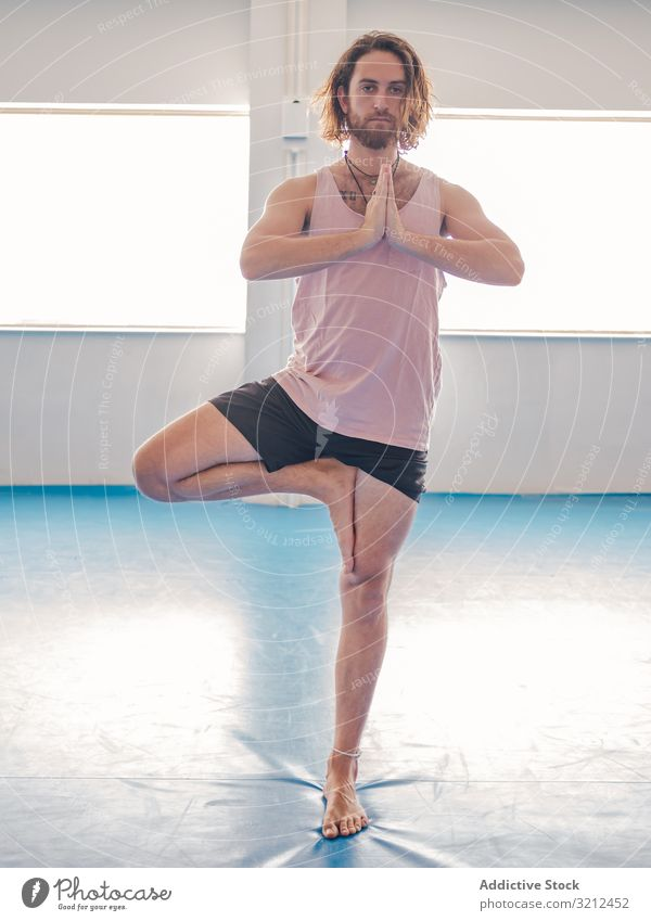 Male doing yoga in spacious room man gym relax vitality zen harmony fitness exercise asana sport young calm peace male bearded happy handsome slender tranquil
