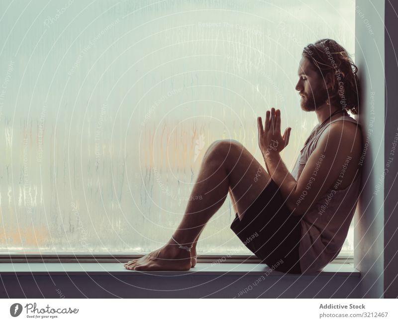 Man in mindfulness on window sill man relax tranquil peace training fitness meditation body lifestyle spiritual health sport windowsill balance sportsman young