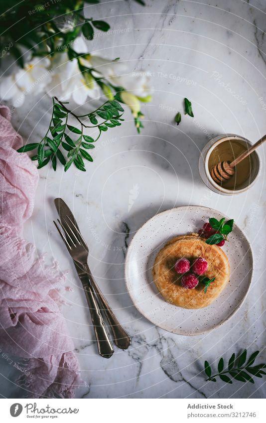 Pancake with fresh raspberry on plate pancake golden brown mint marble tabletop breakfast tasty leaves stylish white serving garnish dessert homemade food