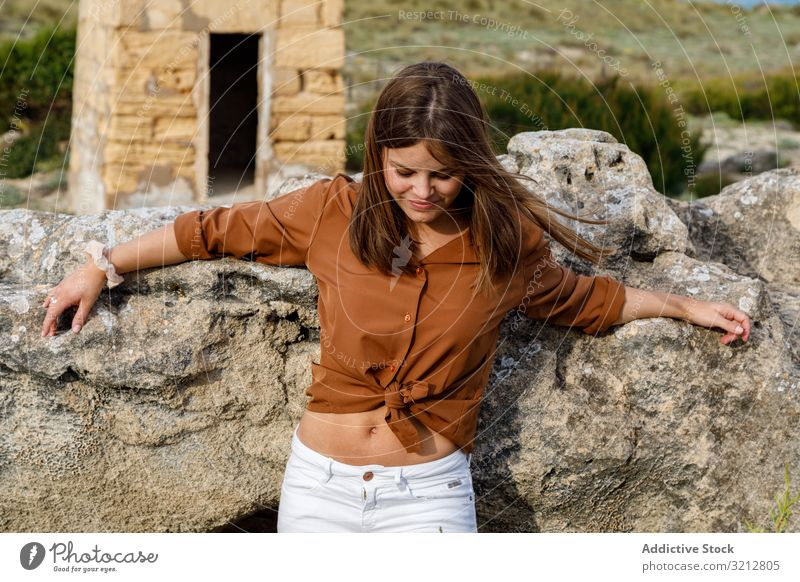 Woman standing near big rock woman stone happy nature carefree field country summer smiling beautiful attractive female enjoy freedom adventure casual tourism