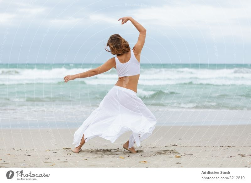 Anonymous woman dancing near sea sand shore freedom concept nature waves weather female movement posture white outfit coast beach ocean water carefree lady