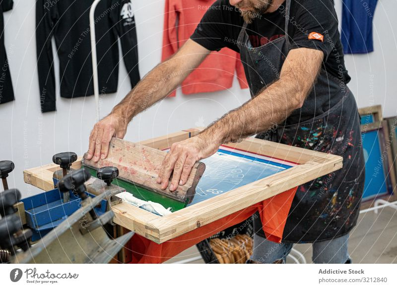 Male artist creating print on t-shirt master screen printing silkscreen serigraphy workshop hobby easel dirty apron style paint modern prepare drawing male