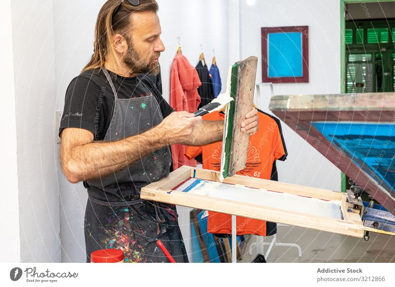 Artist printing screen in workshop artist t-shirt artwork master hobby serigraphy silkscreen creative easel painting drawing male concentration craft occupation