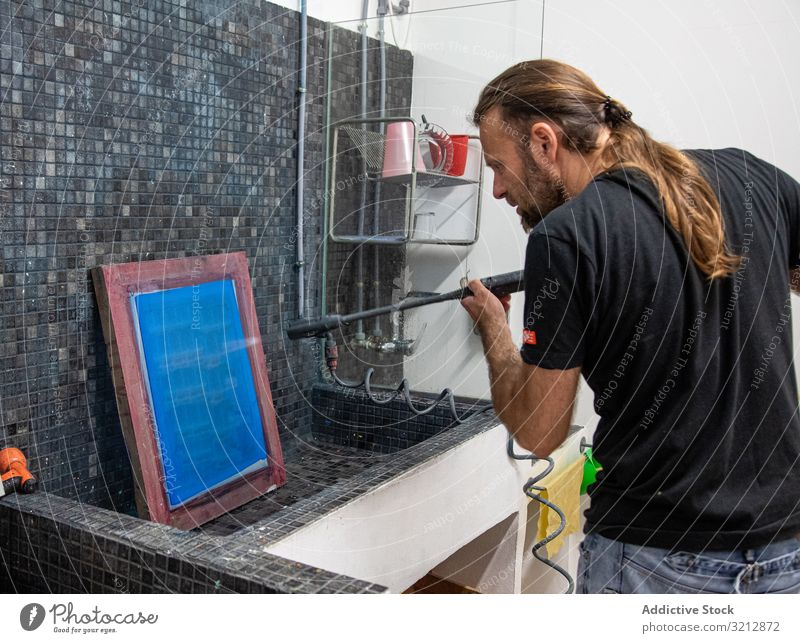 Artist preparing silkscreen for serigraphy artist workshop printing prepare creating man blue hobby easel paint drawing male concentration focused occupation