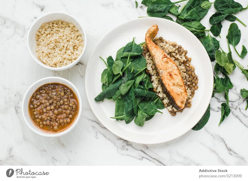 Served salmon steak with beans and couscous spinach greenery tasty delicious served food meal gourmet nutrition dinner spice fish plate bowl diet health dish