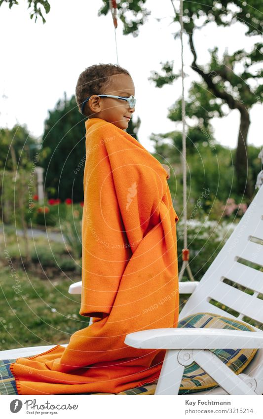 side view of colored boy covered with orange blanket smiling african american beautiful black black people carefree careless cheerful child childhood cute
