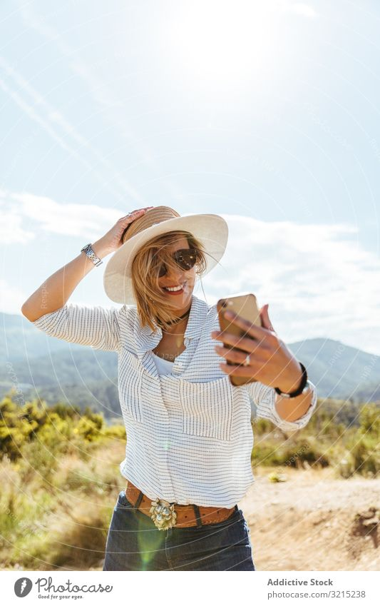 Young girl smiling while looking at her smart phone woman happy sunset using people mobile hat sunglasses young smartphone caucasian person portrait holding