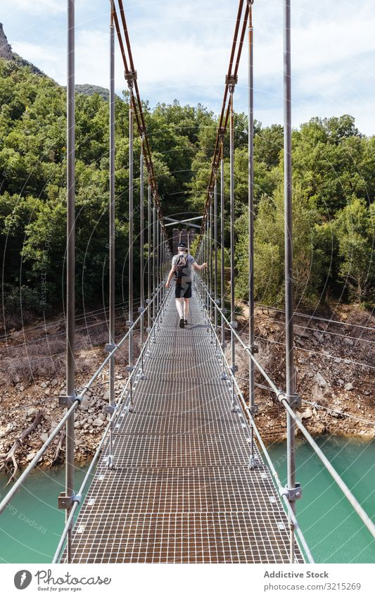 Man crossing a bridge in the mountain man suspension nature person green travel landscape outdoor adventure walk trekking hiking young people tourism river