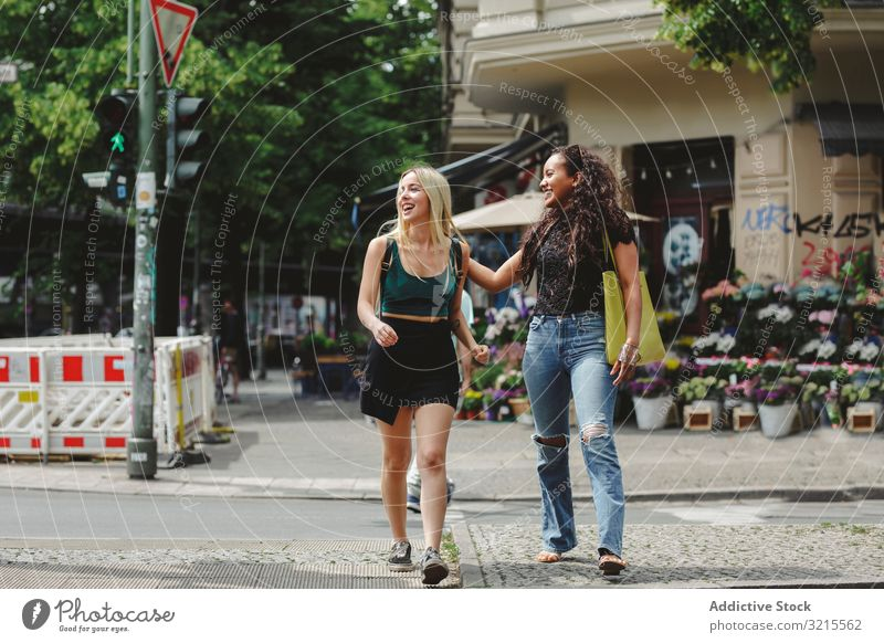 Cheerful friends walking on city street woman berlin summer together bonding smile cheerful young happy girlfriend beautiful sunny trendy casual stylish pretty
