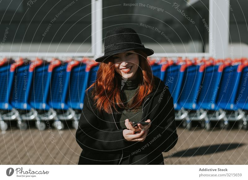 Smiling woman with smartphone in parking lot with shopping carts attractive young beautiful casual cheerful smiling network telephone modern standing joy