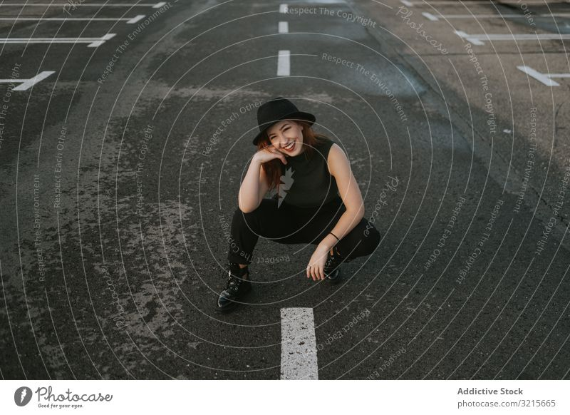 Smiling woman sitting on road with markings attractive empty markup stylish fashion young waiting happy direction model elegant lifestyle beautiful female
