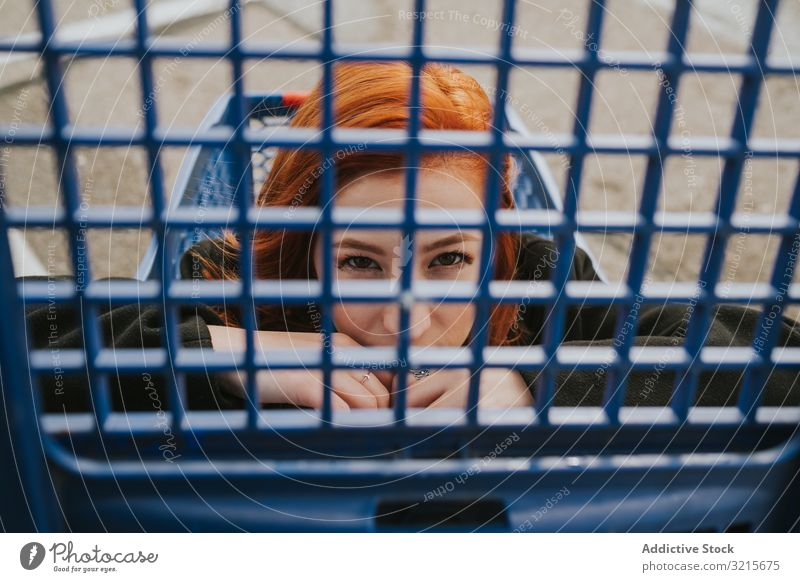 Woman looking through trolley grate in shopping cart woman attractive young beautiful casual cheerful smiling smart modern joy redhead female pretty pleasure