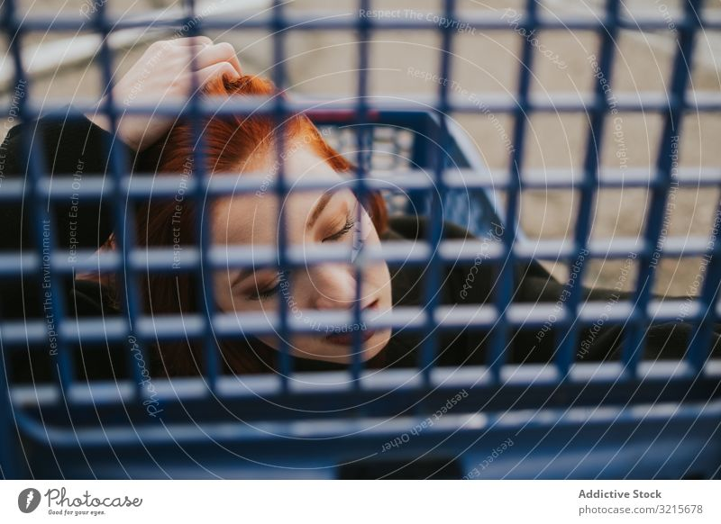 Woman looking through trolley grate in shopping cart woman attractive young beautiful casual smart modern joy redhead female pretty pleasure stylish parking lot