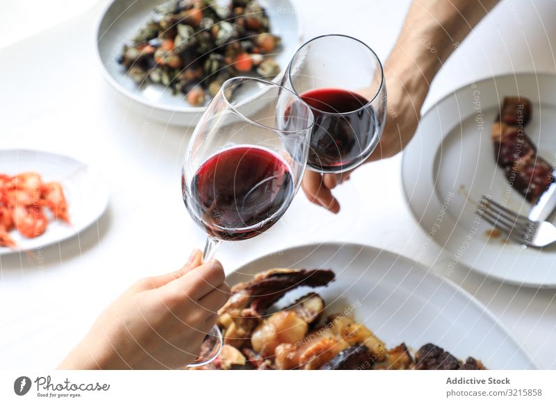Couple cheering with red wine glass dinner celebration alcohol drink beverage food party adult people couple eating toasting drinking delicious tasty crystal