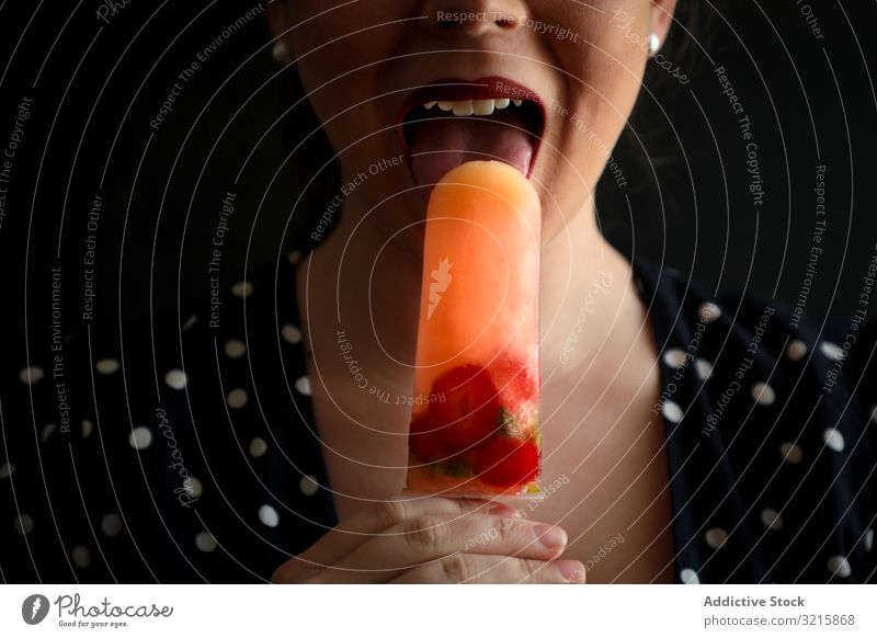 Woman eating fruit popsicle with berries woman berry fresh food lick sensual dessert homemade colorful cool sweet cold ice tasty sorbet natural stick snack
