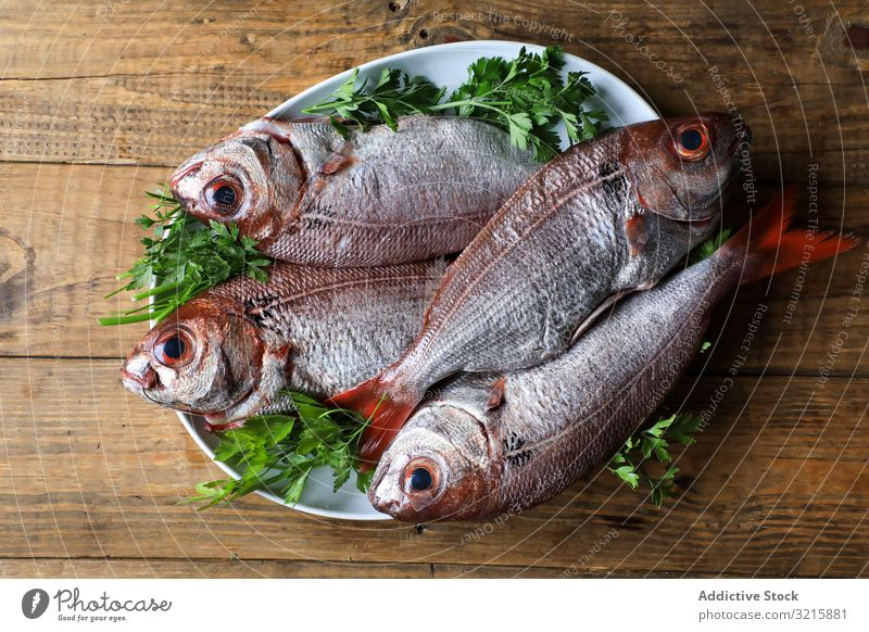 Big fish with red tail in plate seafood parsley fresh cooking appetizing dinner preparation ingredient omega freshness frozen oceanic marine gourmet chop meal