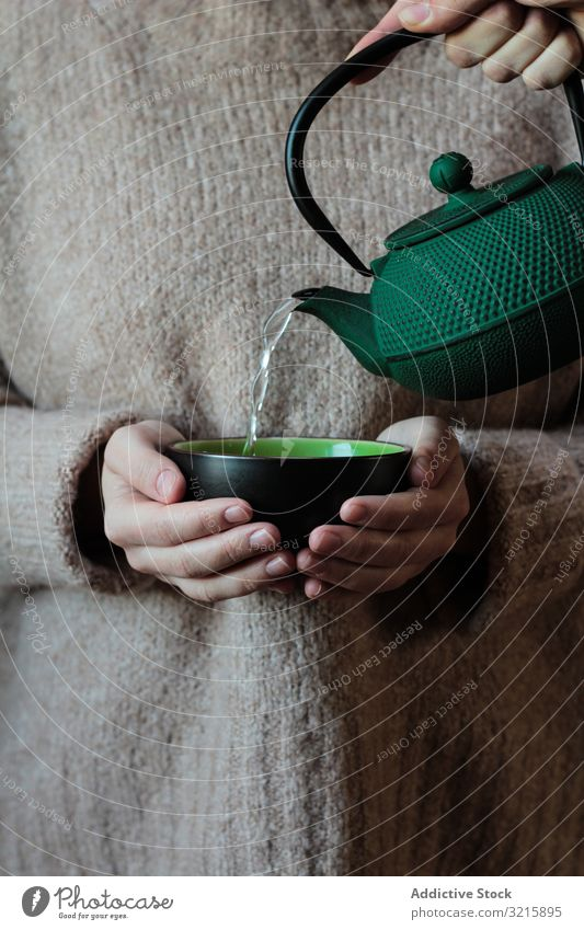 Person pouring tea to cup in hands of woman knitted teapot relaxation drink hot beverage sweater water kettle liquid ceramic holding lady green refreshment