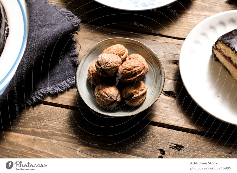 Nuts in bowl cake and napkin on table nuts cloth dessert homemade food bakery cooking sweet brown unpeeled preparation linen ingredient plate snack nutrition