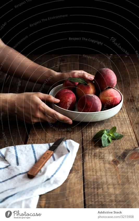 Tasty ripe peaches in plate hands vegetarian food organic fruits raw fresh natural harvest delicious leaf unpeeled plant cut knife juicy refreshment freshness