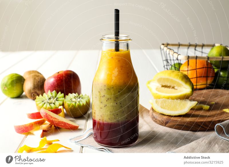 Bottle of layered smoothie fruit layers straw healthy table assorted mix sweet food diet fresh organic glass dessert kiwi apple lemon lime beverage nutrition