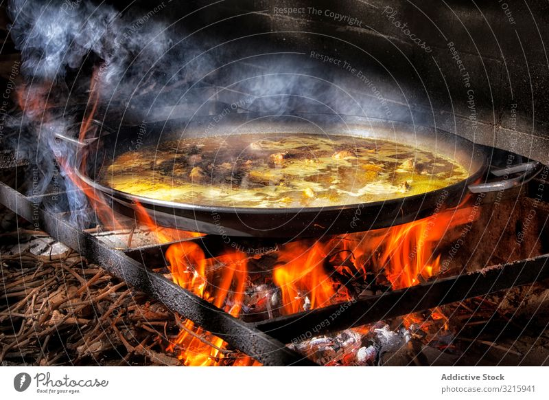 Process of cooking paella on fire rice process cuisine adding spanish traditional food chicken broth flame iron big wood heat hot brick stove dinner seafood