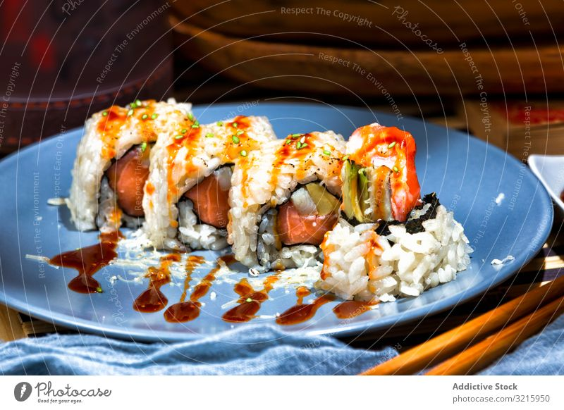 Tasty sushi poured with sauce on blue plate green tasty gastronomy served fish delicious appetizing restaurant asian food dinner salmon meal seafood dish fresh
