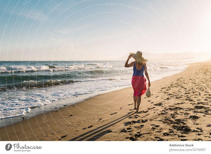 Woman holding hat and walking along seaside woman beach sandy swimwear pareo water ocean summer enjoying leisure athletic sporty body happy slim wavy sunny