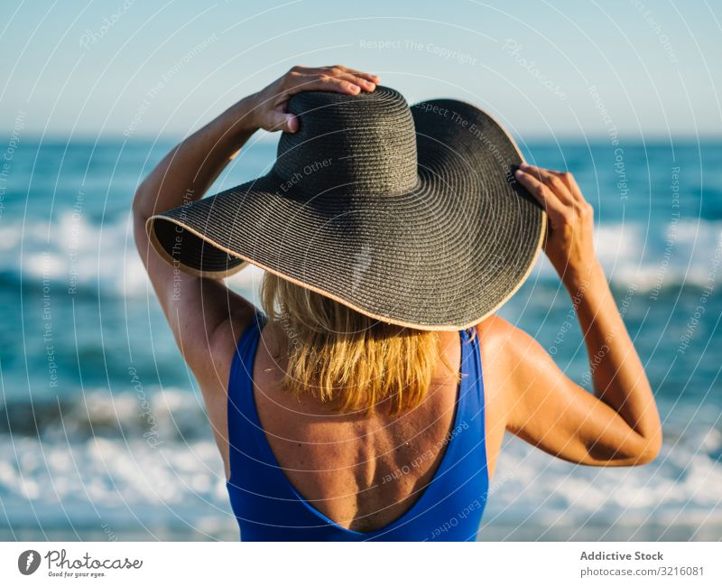 Woman in blue swimsuit and hat on sandy beach woman slim foam swimwear wave water summer leisure tanned attractive seaside covered female turquoise lifestyle