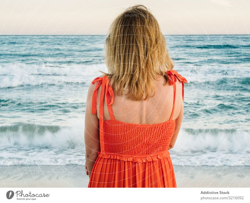 Woman in red dress looking along at seaside woman beach sandy water waves thoughtful enjoying summer relaxing leisure seascape female lifestyle vacation