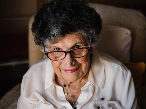 Portrait of aged female in white shirt at home woman grandmother experience wisdom attention grandparent generation senior elderly wrinkle granny gray haired