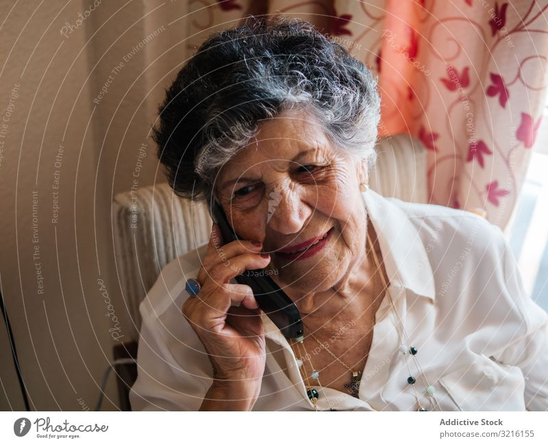 Cheerful elderly woman talking on cell phone at home aged mobile phone grandmother experience wisdom modern conversation attention grandparent generation senior