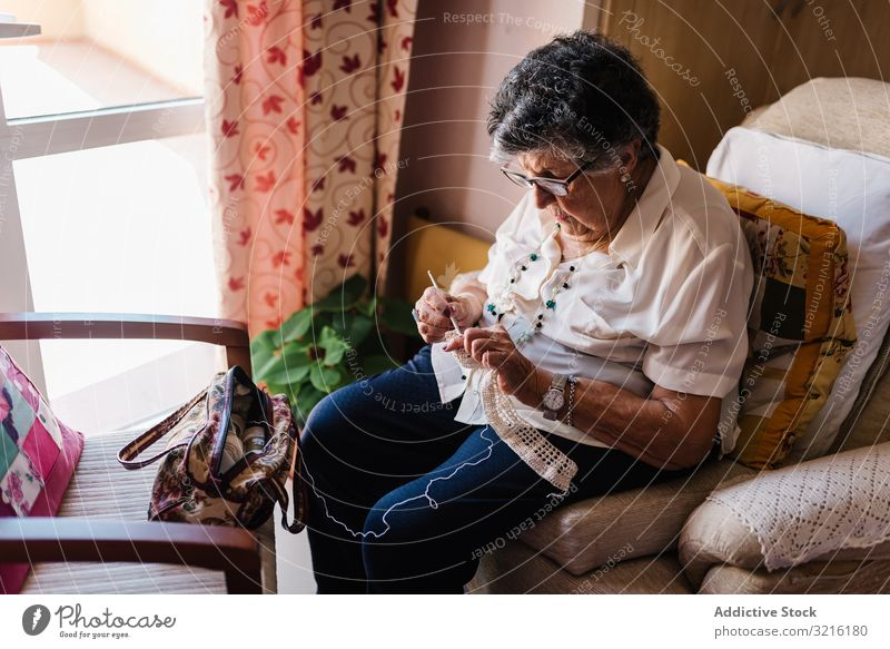 Elderly female taking knitting tools at home aged woman yarn basket experience wisdom grandmother hobby handmade attention grandparent generation senior elderly