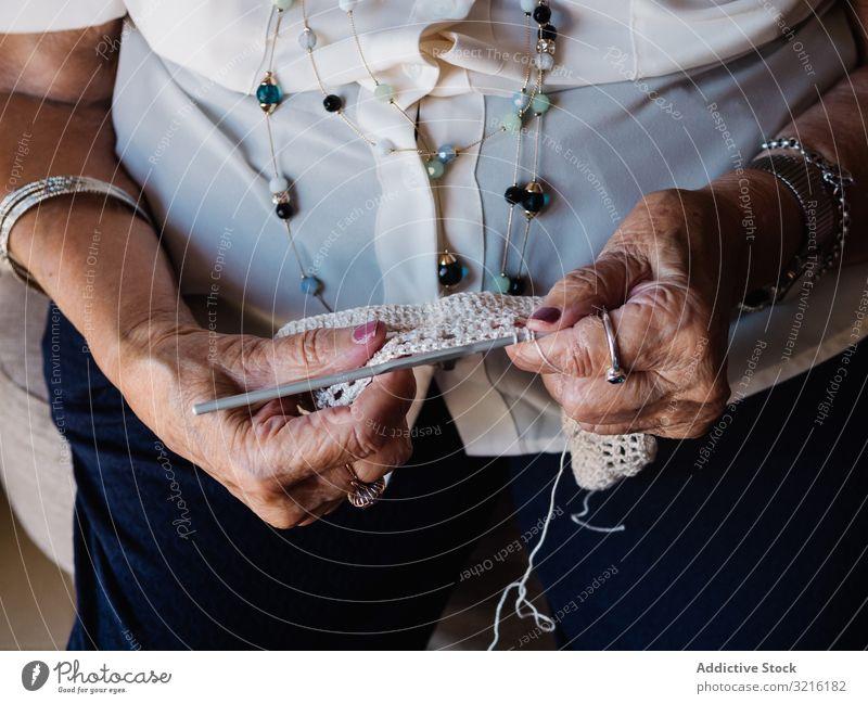 Senior woman knitting crochet aged hobby yarn home experience wisdom handmade grandmother attention grandparent generation senior elderly female wrinkle granny