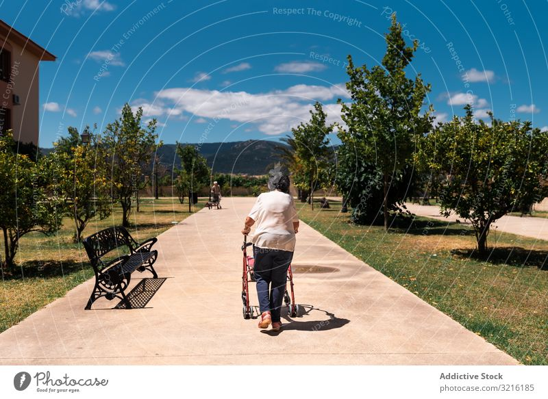 Elderly woman with walker on street aged park experience wisdom activity healthy exercise grandmother attention grandparent generation senior elderly female