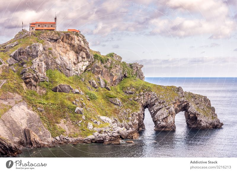 Building on top of stony island among water building seaside calm rocky cloudy sky arch coast nature scenic picturesque landscape travel vacation peaceful