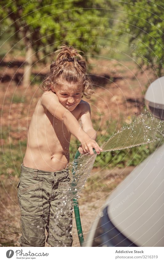 Energetic boy in shorts hosing grey car washing hose water cheerful activity helping splash happy wet spray child fun clean smiling kid cute summer foam