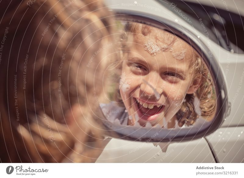 Cute boy smiling and reflecting in car window water cheerful foam activity front mirror helping washing splash happy wet child fun clean kid cute summer