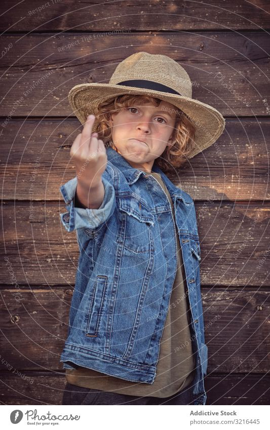 Cheeky self confident boy gesturing fuck you standing kid little middle finger obscene showing fun casual summer funny child active freedom hand adorable