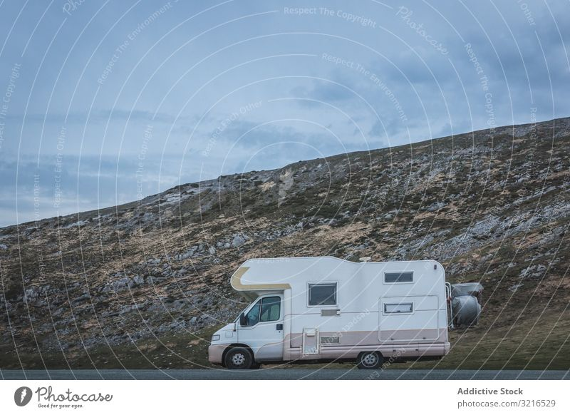 Camper near hill on cloudy day camper travel countryside slope sky road weather vehicle parked auto transport trailer caravan adventure trip journey tourism