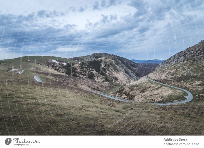 Winding road on hilly terrain countryside cloudy sky narrow winding slope grass nature landscape rural scenic dramatic path way track trail overcast curve