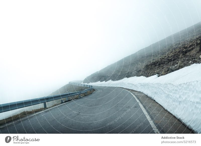 Road in foggy mountains road travel nature landscape weather mist haze vague slope terrain trip journey tourism adventure gray snow cold cool highway trail