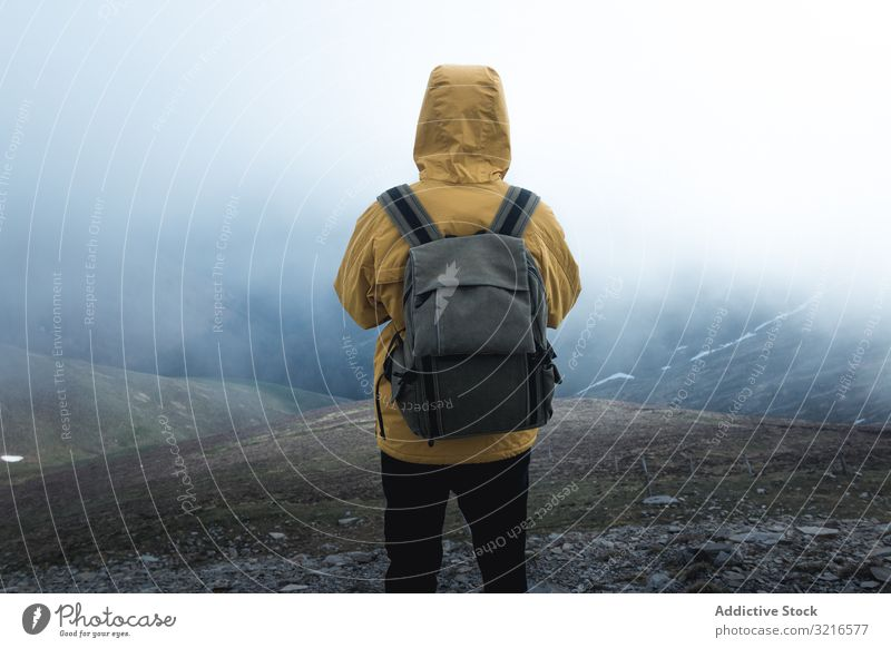 Anonymous traveler on hill on misty day man hillside fog nature weather backpack stand countryside hiking male trekking trip journey tourism adventure slope