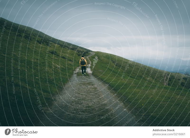 Anonymous traveler standing on road on hillside man countryside cloudy sky narrow rough grass green nature slope landscape rural scenic terrain path way track