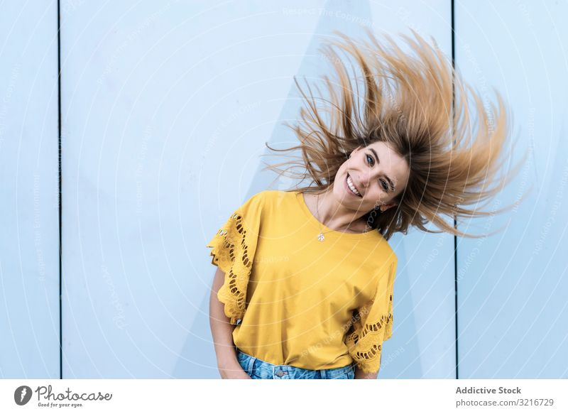 Young woman shaking hair silly shake happy young cheerful smiling long hair beautiful look female attractive yellow model gorgeous summer positive color trendy