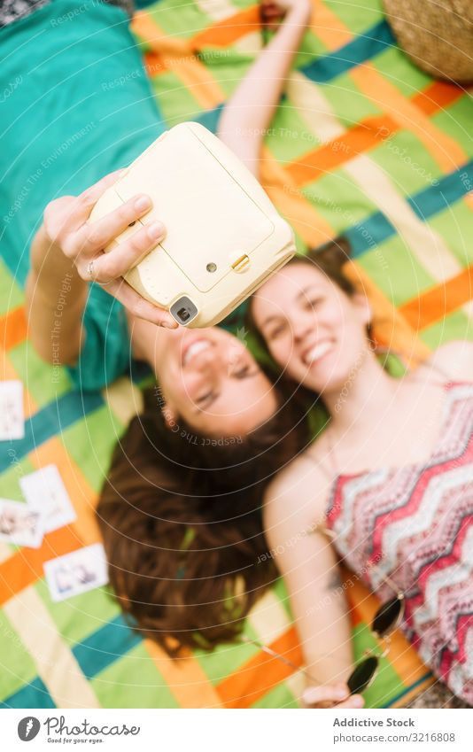 Smiling women in sunglasses taking instant photo on plaid woman taking selfie summer best friend memory photo camera style vacation leisure beautiful moment