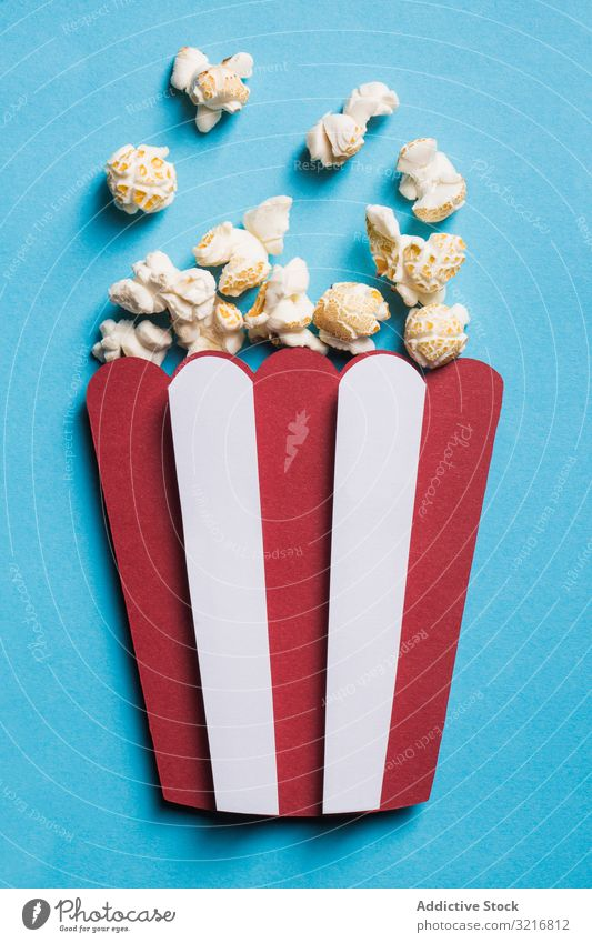 Silhouette of a popcorn box made of cardboard with real popcorn art cinema collage colorful composition concept conceptual craft creativity disposable flat lay
