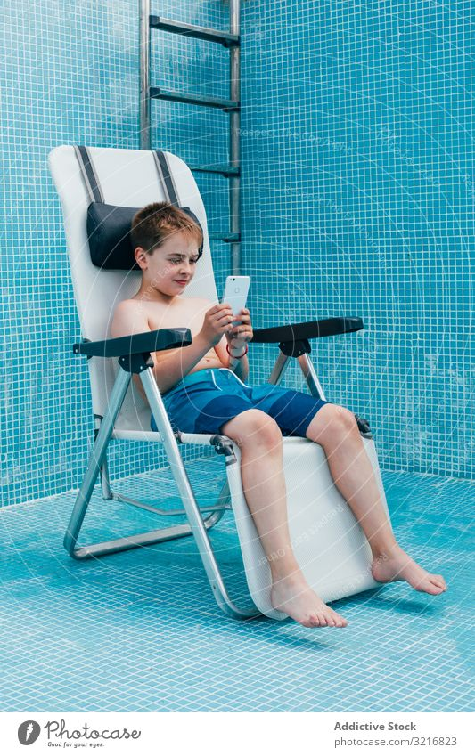 Boy with smartphone sitting on bottom of empty pool boy kid resting chair tile decorated technology gadget device mobile play child vacation childhood game
