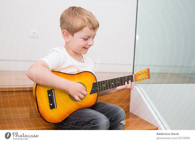 Young blonde boy playing toy guitar music instrument kid hobby musician talented child little male casual cute adorable concentrated sitting practicing white