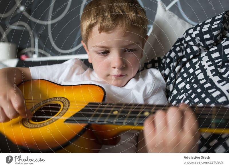 Young blonde boy playing toy guitar music instrument kid hobby musician talented child little male person casual cute adorable lying relaxing practicing white