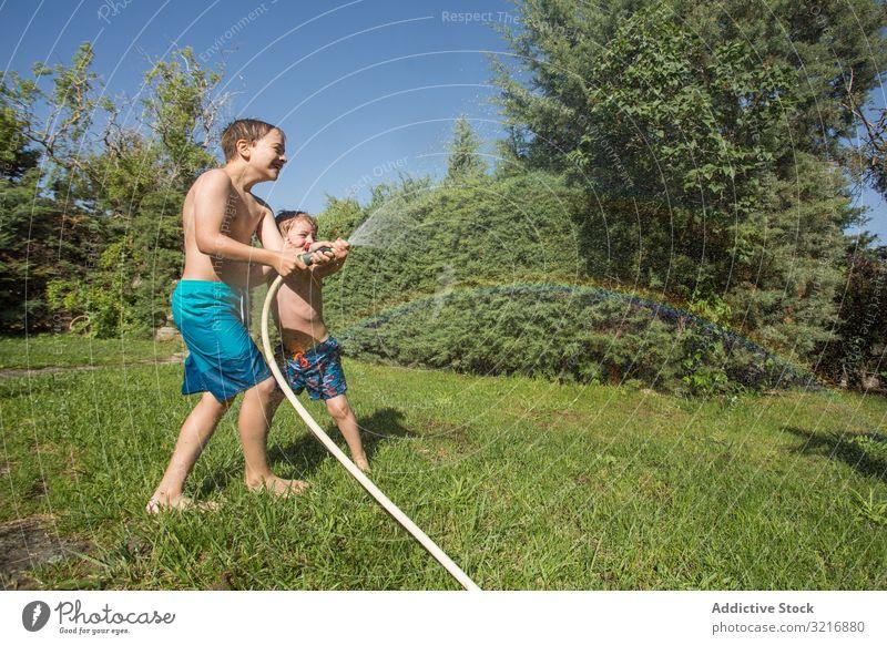 Little kids in swimwear having fun with splashing water children summer playing happy holding lifestyle leisure recreation holiday childhood joy enjoyment